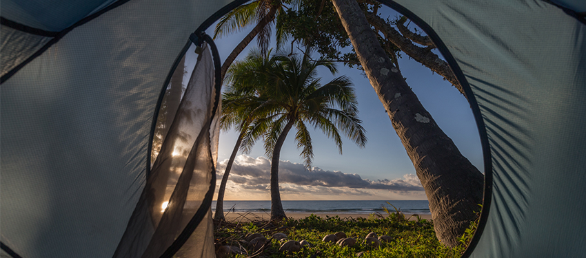 View of the beach and sunrise from inside tent.